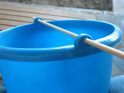 A wooden dowel inserted through two holes near the rim of a plastic bucket