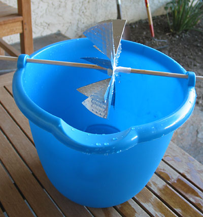 A waterwheel cut from an aluminum pie pan held over a plastic bucket by a wooden dowel
