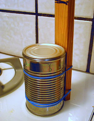 An upside-down steel can is attached to a wooden stick with rubber bands