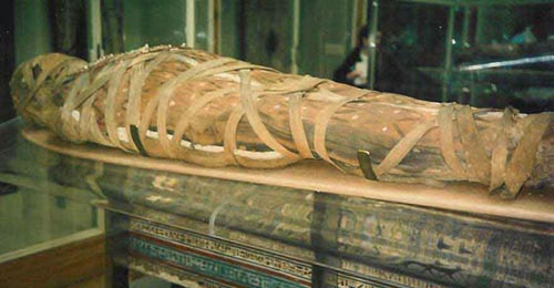 A partially wrapped and mummified Egyptian body resting on a platform