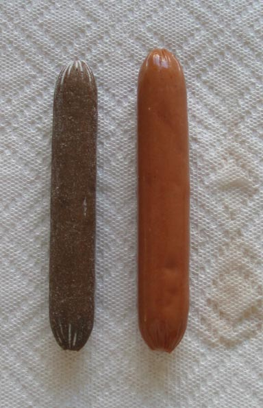 A discolored and mummified hot dog placed to the left of a fresh non-mummified hot dog