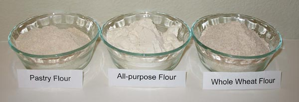 Photo of three small bowls side-by-side filled with different types of flour and labeled from left to right: Pastry Flour, All-purpose Flour, and Whole Wheat Flour.