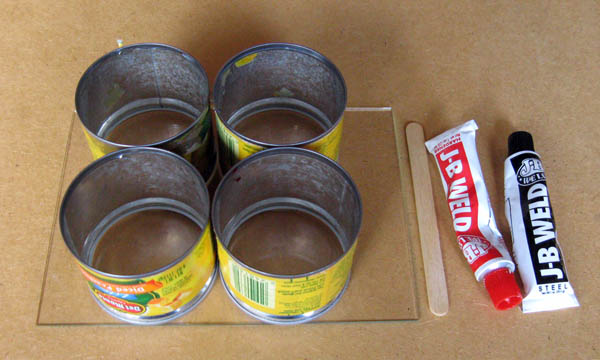 Four tin cans, a small glass pane, a popsicle stick, and two tubes of a two-part epoxy