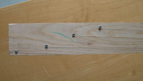 Four screws are placed diagonally on the length of a wooden plank starting from the bottom left and ending in the top right