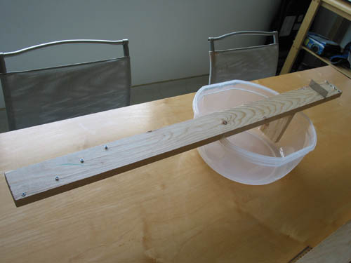 A homemade banjo consisting of a wooden plank, plastic tub, fishing line, screws and a metal bridge