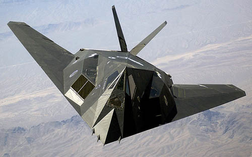 This photo shows a military aircraft in flight over a desert. The cockpit and body of the plane have a squashed diamond shape. The tail is a thin v-shape behind the body, and the wings are a V-shape also, and continuous with the cockpit and the body. The plane is painted a matte black finish.