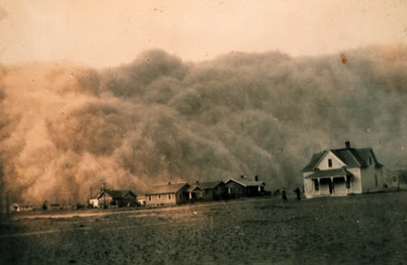 This black and white photo shows a dust storm in Texas on April 18, 1935. A huge dust cloud is approaching houses and people standing in a field.