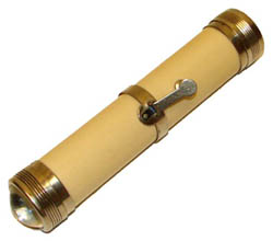 This photo shows a flashlight from 1899. It is beige narrow cylinder with metal rings around each end and a metallic switch around its middle. One end also has a convex light.