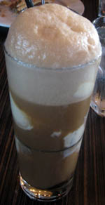 This photo shows a tall glass containing root beer and vanilla ice cream topped by a thick foam which is nearly spilling out of the glass.