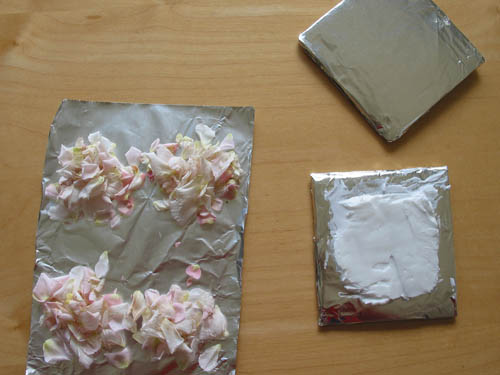 Vegetable shortening spread over an aluminum foil square next to four piles of flower petals