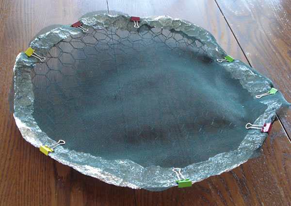 Chicken wire and mesh are cut into a large circle and held together with aluminum foil and binder clips