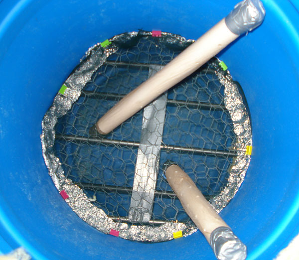 A chicken wire and mesh circle lie on top of metal rods at the bottom of a plastic barrel