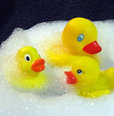 Three rubber ducks float in soapy water