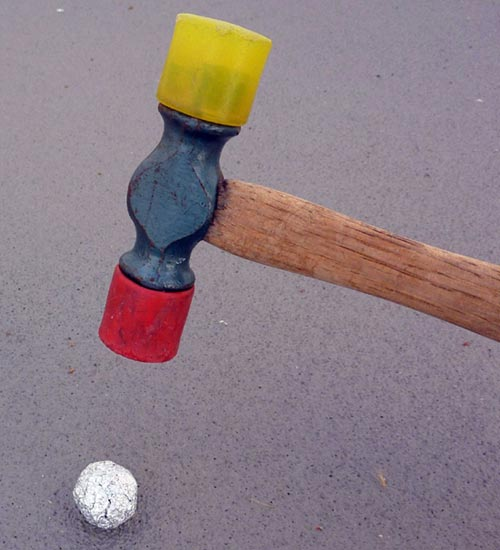 A rubber mallet is used to compact an aluminum foil ball