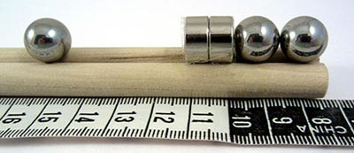A metal ball bearing next to a group of two metal ball bearings attached to two circular magnets