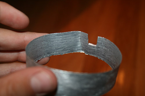 An aluminum ring has a small square notch cut from one of its sides