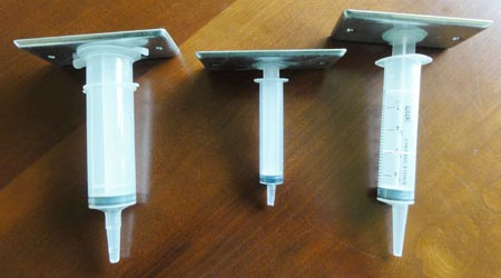 Metal plates are placed on the plungers of three different sized syringes