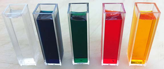 Five cuvettes filled with water with four being colored with food coloring (blue, green, red and yellow)