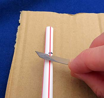 Notches are cut in a plastic straw using a razor blade