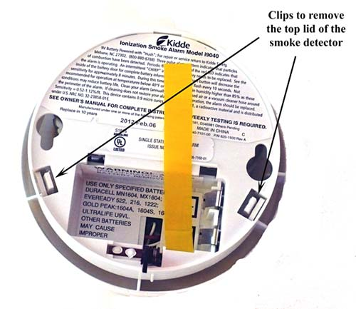 On the back of the smoke detector, open the battery compartment first and then push on the clips to remove the top lid..
