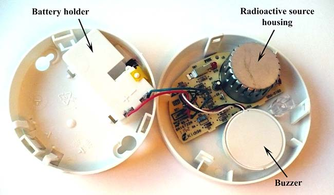 Picture of a smoke detector with the top lid removed. The beige semicircle is the circuit board.