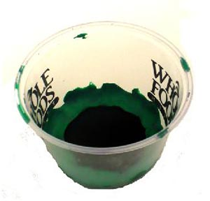 Felt lines the inside bottom of a plastic cup and is held in place with clay pressed along the edge of the felt