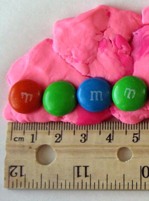 Math science project  Photo of M&M's lined up length-wise by ruler.