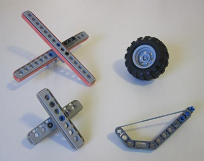 Various Lego attachments wrapped in rubber bands next to a rubber Lego wheel