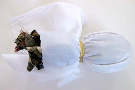 White cloth covers an egg that is wrapped in a tie and is secured with a rubber band