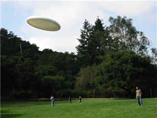 Photo of a frisbee gliding through the air at a park