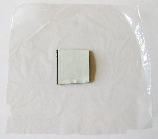 Human Biology science project Picture of a magnet tape square on a piece of plastic wrap.