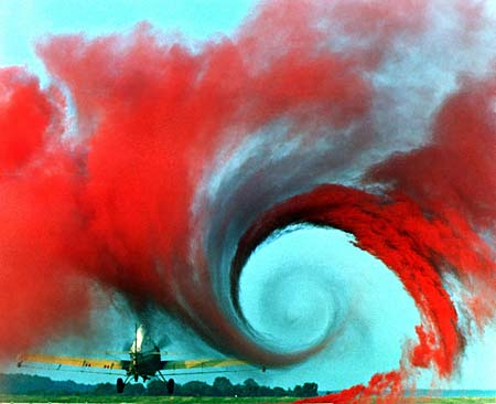 Red smoke is used to show a vortex of air created behind the wing of an airplane