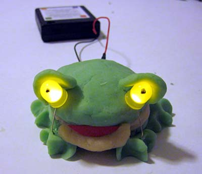 A frog is made of model clay and has two LEDs for eyes that are powered by a battery pack