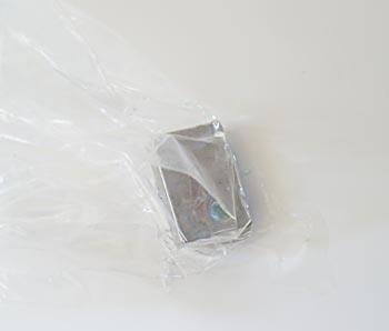Neodymium bock magnet put in the corner of a sandwich bag, ready to pick up the magnetized oil spill in an oil clean up procedure