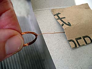 Sandpaper is used to remove the top-half of insulation from a single axle of a coiled wire