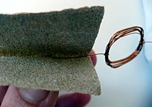 Sandpaper is used to remove all of the insulation from a single axle of a coiled wire