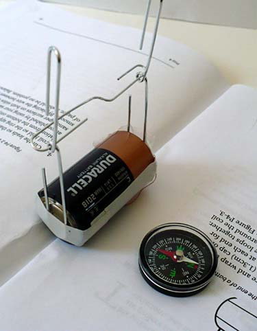 A paperclip is suspended between two paperclips that are taped to the terminals of a C cell battery next to a compass