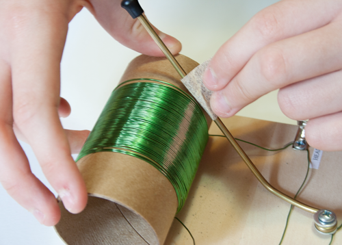Insulation on a copper tuning rod, in a homemade crystal radio, is removed with sandpaper