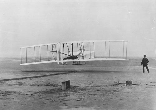 Black and white photo of the Wright Flyer in the air.