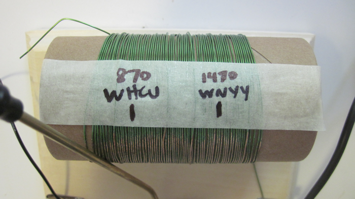 Tape across the tuning coil of a homemade crystal radio is marked with the positions of certain radio broadcast stations