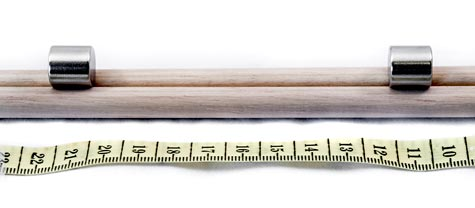 Photo of two magnets spaced along a wooden dowel.