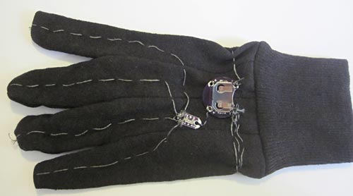 Conductive thread, a switch and a battery holder sewn onto the back of a glove