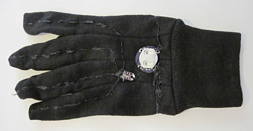 Conductive thread sprayed with paint, a switch and a battery holder sewn onto the back of a glove