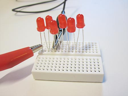 Two alligator clips connect to two different LEDs in a breadboard