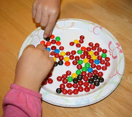 Two hands pick up M&M candies off of a plate