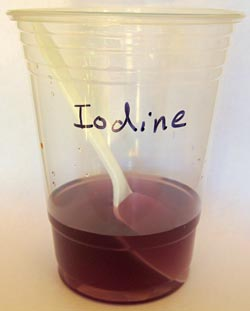 A violet colored solution and plastic spoon sit in a plastic cup labeled iodine