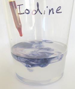 Liquid from an eye dropper reacts with clear liquid in a plastic cup turning the clear liquid blue