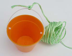 String is tied to the handle of a small bucket