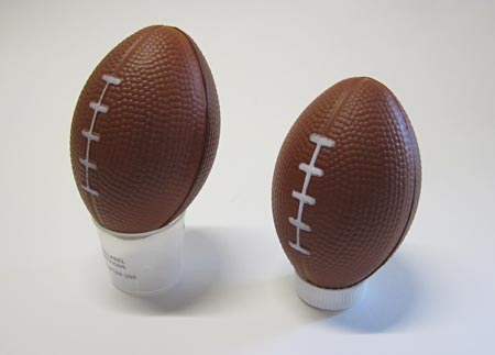 Small footballs resting on medicine cup or small bottle cap