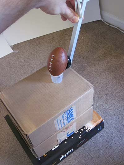 A small football rests on various textbooks and a cardboard box